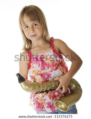 A pretty young elementary girl happily holding a toy gold saxophone.  On a white background.