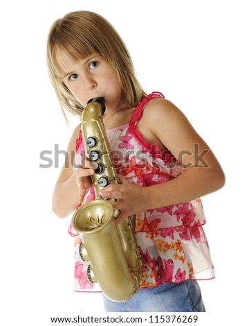 A pretty young elementary girl with puffed out cheeks, as she plays a toy saxophone.  On a white background.