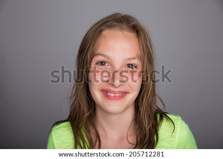 A pretty young freckle faced girl with a happy smile - stock photo