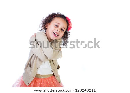 A pretty young girl hugging herself with a big smile on her face. - stock photo