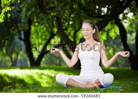 A pretty young girl in lotus position - stock photo