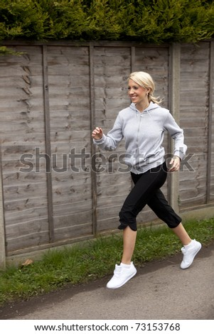 a pretty young girl outside running along a path - stock photo