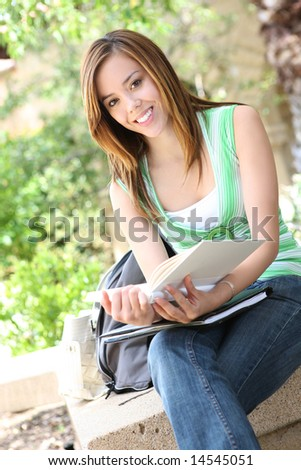 A pretty young girl reading a book on the school campus - stock photo