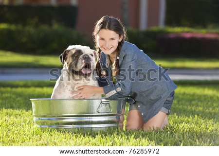A pretty young girl washing her her pet dog, a bulldog, outside in a metal bath tub