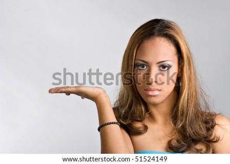 A pretty young hispanic woman holding her hand out with plenty of copy space.  Easily place your own object or text on her hand. - stock photo