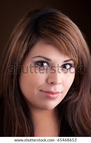 A pretty young Hispanic woman with a smile on her face and highlighted hair. - stock photo