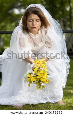 A pretty young summer bride distressed on her wedding day.   - stock photo
