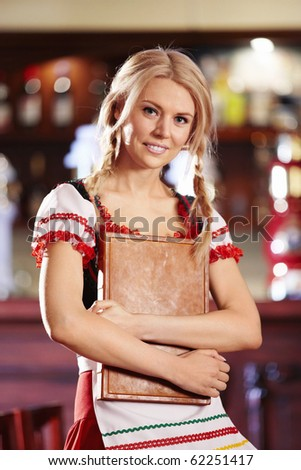 A pretty young waitress holding menu in his hand - stock photo