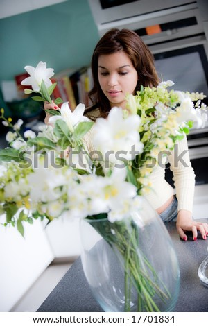 A pretty young woman arranging flowers in the kitchen - stock photo