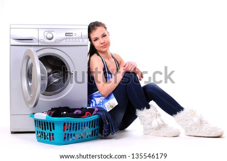 A pretty young woman doing laundry - stock photo