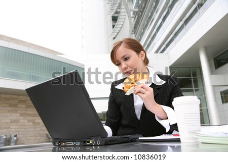 A pretty young woman eating and working on computer - stock photo