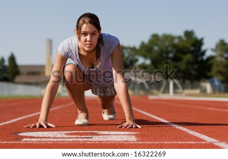 A pretty young woman exercising at a race track - stock photo