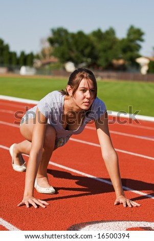 A pretty young woman exercising at the race track - stock photo