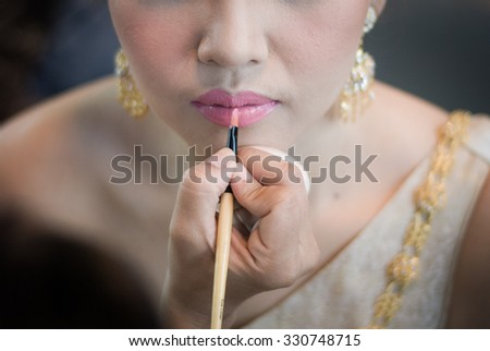 A pretty young woman getting ready for her wedding and having her lipstick applied. - stock photo