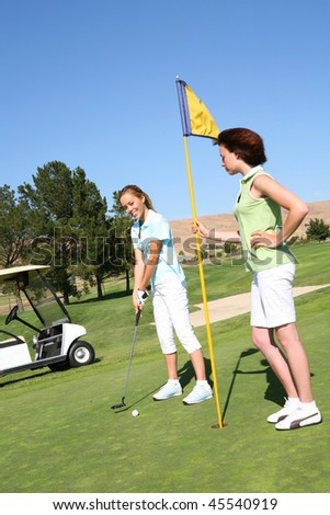 A pretty young woman golfer playing golf with friend - stock photo