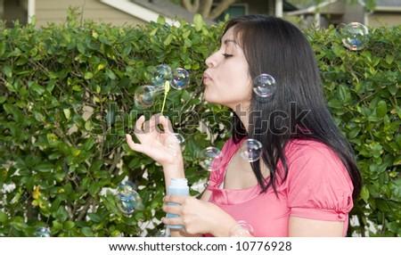 A pretty young woman having fun blowing bubbles. - stock photo