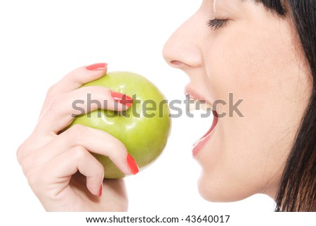 A pretty young woman holding an apple she's about to eat - stock photo