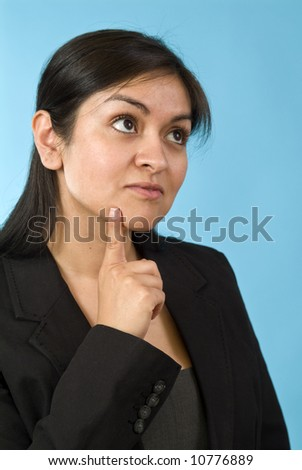 A pretty young woman holding her finger to her chin in a gesture of wondering or pondering. - stock photo