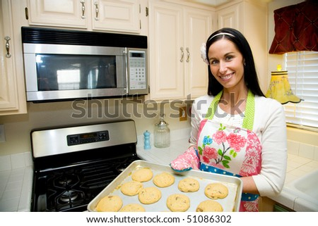 A pretty young woman in a colorful apron is baking cookies in her clean, modern kitchen - stock photo