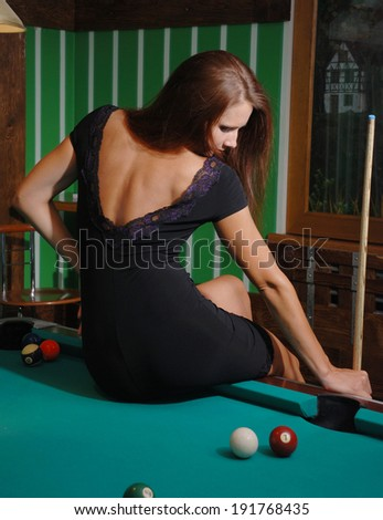 A pretty young woman is sitting on the billiard-table.