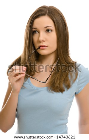 A pretty young woman, isolated against a white background, holds a pair of glasses as she thinks - stock photo