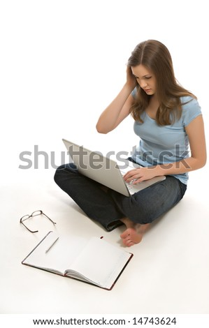 A pretty young woman, isolated against a white background, works on her laptop. - stock photo