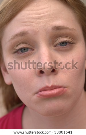 A pretty young woman looks at the camera with a pouty look on her face. - stock photo