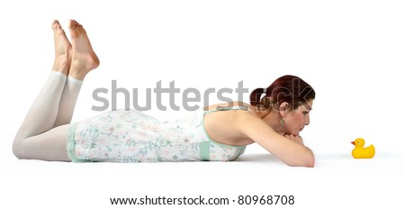 A pretty young woman lying on the floor in her night gown while looking at a rubber duck - stock photo
