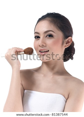 A pretty young woman makeup her face with brush - stock photo