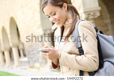 A pretty young woman on the cell phone on the school campus - stock photo
