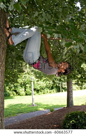 A pretty young woman playfully hangs from a tree limb. - stock photo