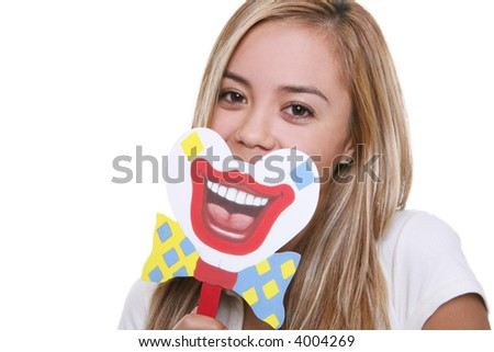 A pretty young woman putting on a happy clown face - stock photo