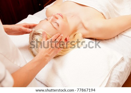 A pretty young woman receiving a scalp massage in a spa - stock photo