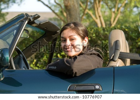 A pretty young woman sitting in a convertible sports car smiling warmly. - stock photo