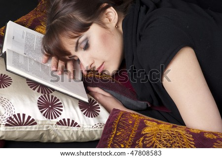 A pretty young woman sleeping  after reading a book on pillows - stock photo