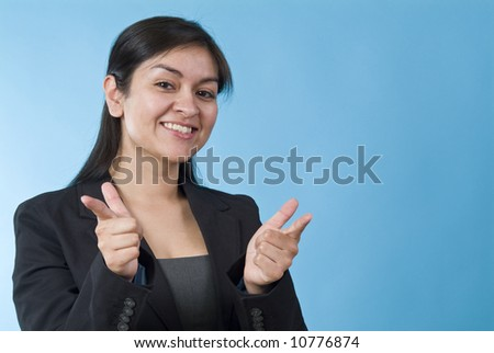 A pretty young woman smiling and making a affirming, pointing gesture at the camera. - stock photo