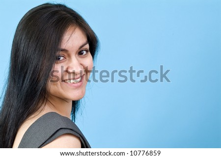 A pretty young woman smiling coyly for the camera taken against a blue background with copy space. - stock photo