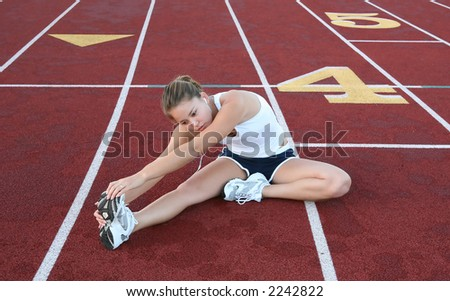 A pretty young woman stretching before jogging - stock photo
