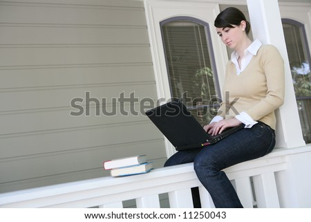 A pretty young woman student working on laptop computer