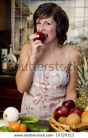 A pretty young woman taking a bite out of an apple - stock photo