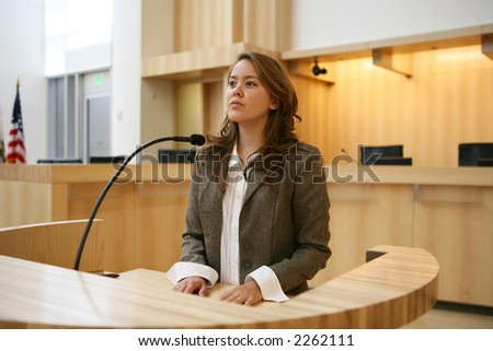 A pretty young woman testifying in court - stock photo