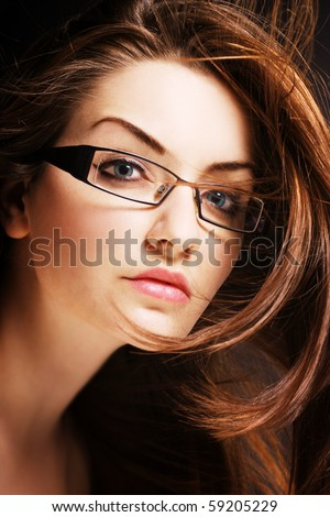 A pretty young woman wearing modern glasses with wind in her hair. - stock photo