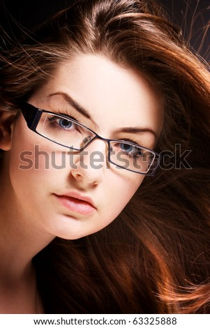 A pretty young woman wearing modern glasses with wind in her hair.
