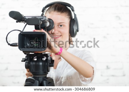 a pretty young woman with a professional camera and headphone