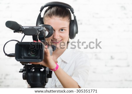 a pretty young woman with a professional  movie camera and headphones
