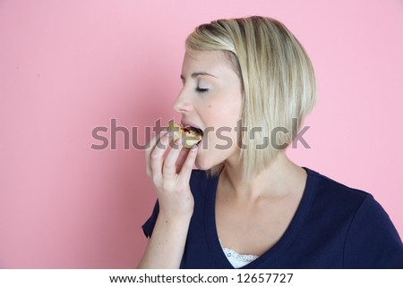 A pretty young women takes a bite from a cake