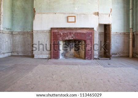 A previously formal room with fireplace and blank picture over the mantal, in an old long abandoned large house.  Looks to be in dire need of repair. - stock photo