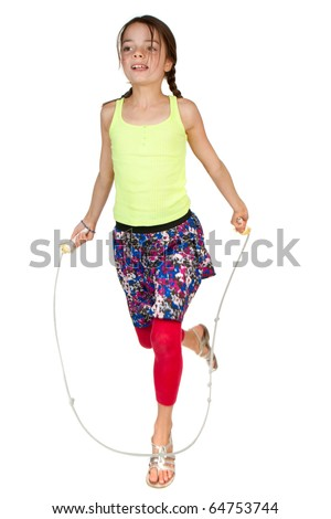 A primary aged girl jumping over a skipping rope.