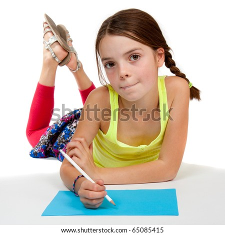A primary aged girl looking thoughtful whilst drawing on some blue paper. - stock photo