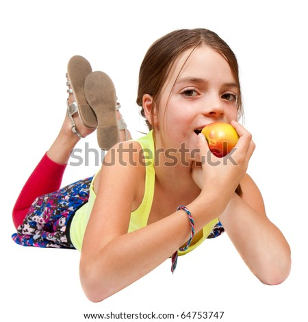 A primary aged girl lying down and eating an apple.  Studio isolated on white.